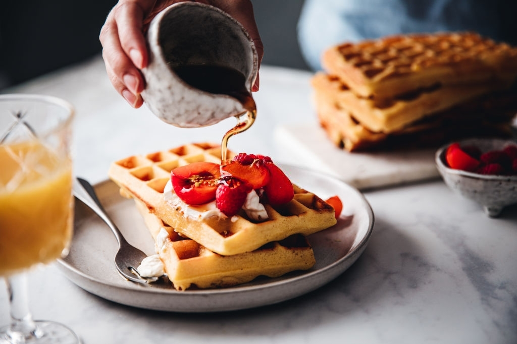 Close-up of a female hand pouring maple syrup on waffle. Woman serving sweet and tasty breakfast.